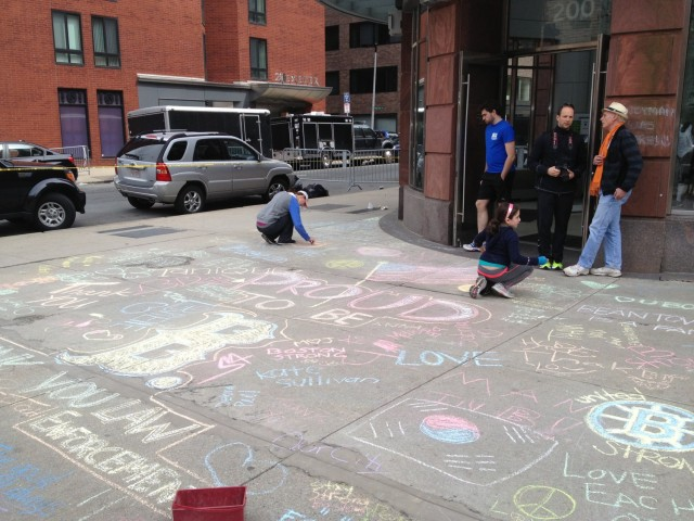 Writing sentiments on chalk on sidewalk