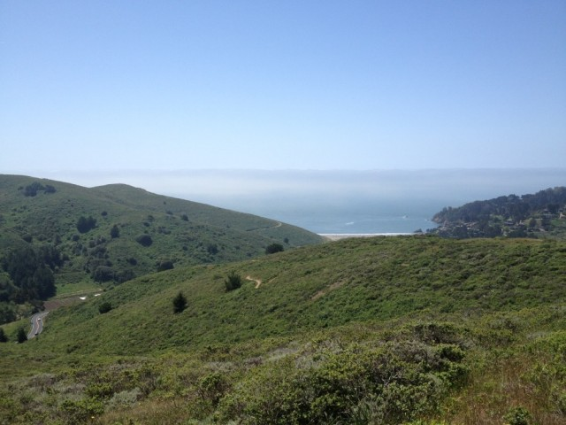 View of Pacific Ocean in distance beyond green hills
