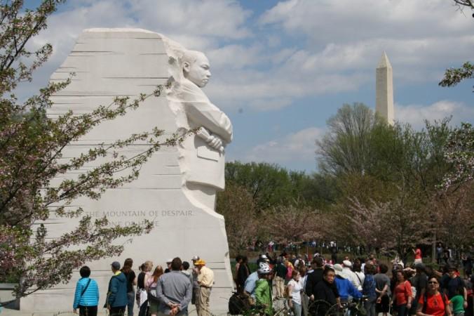 Crowd of people along base of memorial.