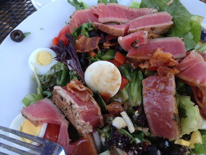 Slices of rare tuna, hard boiled eggs, black olives, and bacon on lettuce.