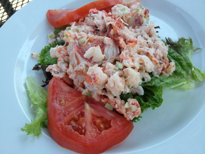 Chunks of lobster salad over lettuce with slices of tomato